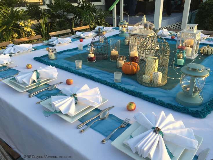 Outdoor dinner party with candles, cloth napkins and teal and white linens